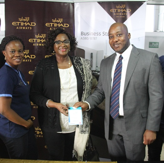 L-R: Folasade Akinboro, Etihad Airways' Marketing Officer (left) and Percival Uwechue, Etihad Airways' Airport Manager (right) hand over a complimentary Wi-Fi voucher to a premium guest on arrival at check-in..
