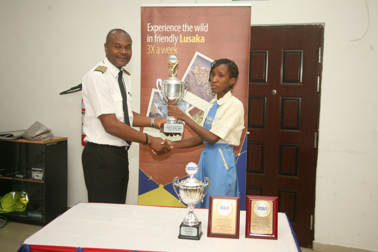 Capt. Jim Hassan, Training Manager, Nigerian College of Aviation Technology (NCAT), Zaria presenting a trophy to Miss Igweonu Chiamaka, a student of Murtala Muhammed Airport Secondary School (MMASS), Ikeja, 2nd place Winner, NTEC 2015/2016 and beneficiary of a free ticket to Accra, Ghana sponsored by Med-View Airlines.