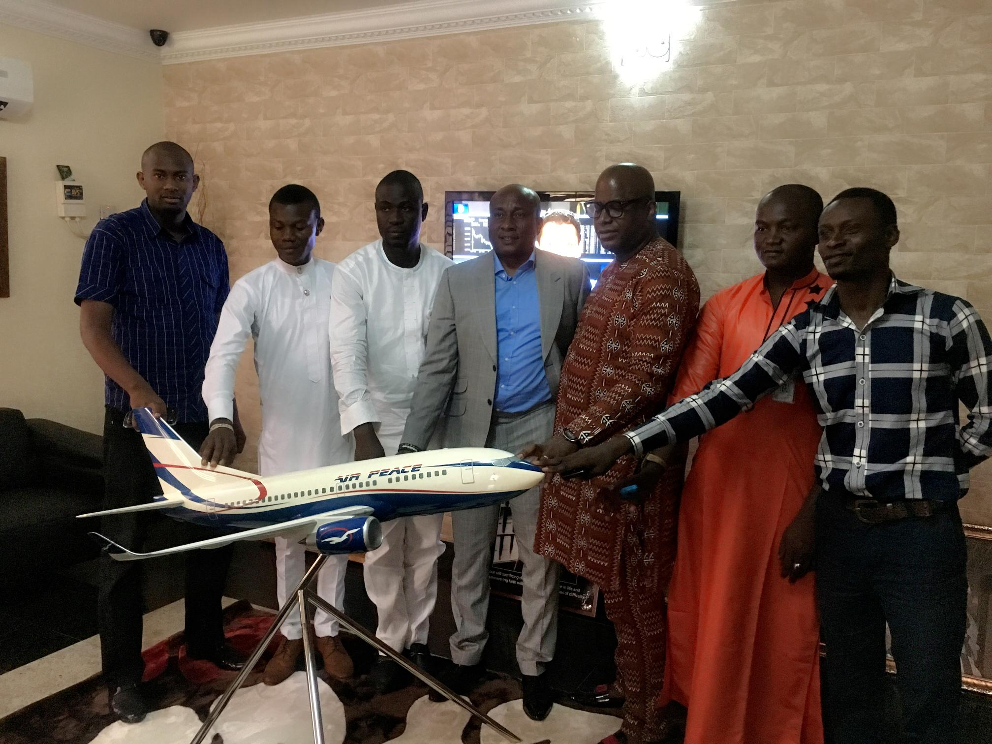 Chairman/Chief Executive Officer of Air Peace, Barr. Allen Onyema (middle), Senate President of the National Association of Nigerian Students (NANS), Comrade Salam Oyejide (3rd left), other executive members of NANS and the Grand Patron of the association in Akwa Ibom State, Mr. Ubong King (3rd right) placing their hands on Air Peace's model aircraft to symbolise their endorsement of the airline as the official carrier of Nigerian students during their visit to the corporate headquarters of the airline in Lagos.