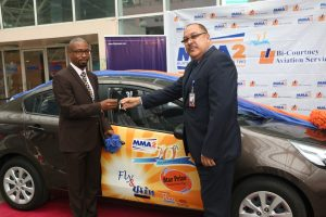 Chief Executive Officer, Bi-Courtney Aviation Services Limited (BASL), a member of The Resort Group and operators of the Murtala Muhammed Airport Terminal Two (MMA2), Captain Jari Williams (right) presenting the keys of a Kia Rio car, the star prize in the just-concluded MMA2 @ 10 Fly and Win promo, to the winner, Mr. Polycarp Anyanwu, an official of the National Pensions Commission (PenCom), Abuja.